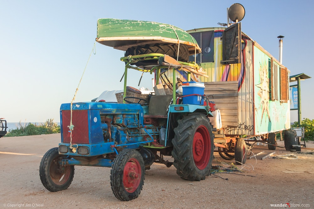 A farm tractor pulling a colorful wagon full of toys while traveling the world