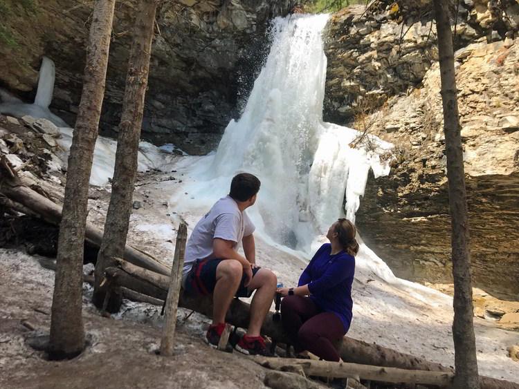 An image of a couple looking back at Troll Falls in Kananaskis, Alberta
