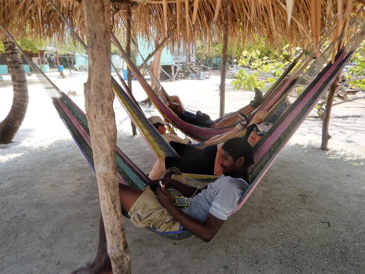 Four people relaxing in hammocks in Belize