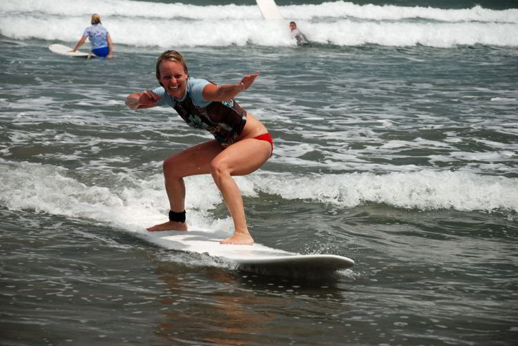 An image of a woman riding a wave at Anamaya Resort in Costa Rica - Yoga Retreat Costa Rica