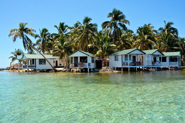 An image of five over water cabins of Tobacco Caye Paradise on the island of Tobacco Caye in Belize