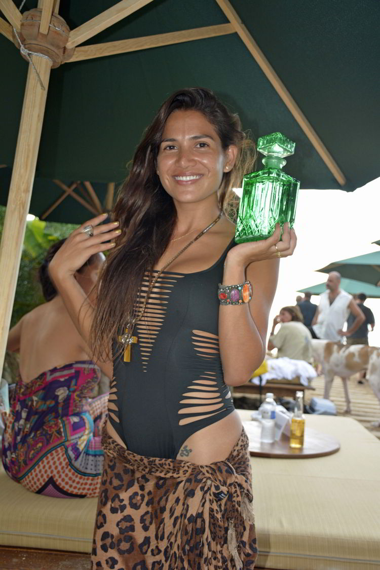 An image of a woman holding a fancy tequila bottle at a beach bar in Yelapa - Jalisco, Mexico - Yelapa Beach