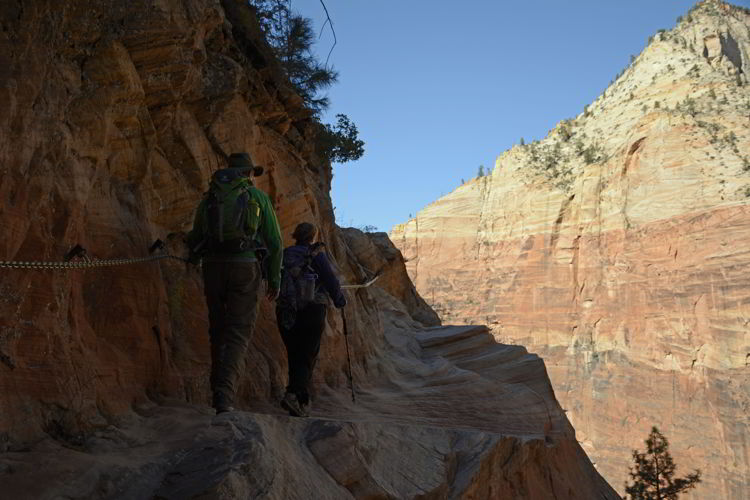 An image of two people grasping a chain as they climb the trail to Hidden Canyon Trail in Zion National Park in Utah - Best Zion National Park Hikes