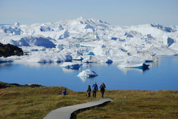 An image of three people walking on th boardwalk to reach the Ilulissat Icefjord in Ilulissat, Greenland