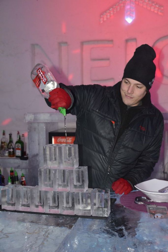 An image of a bartender pouring drinks at the ice bar at the Hôtel de Glace in Quebec, Canada - Ice Hotel Quebec