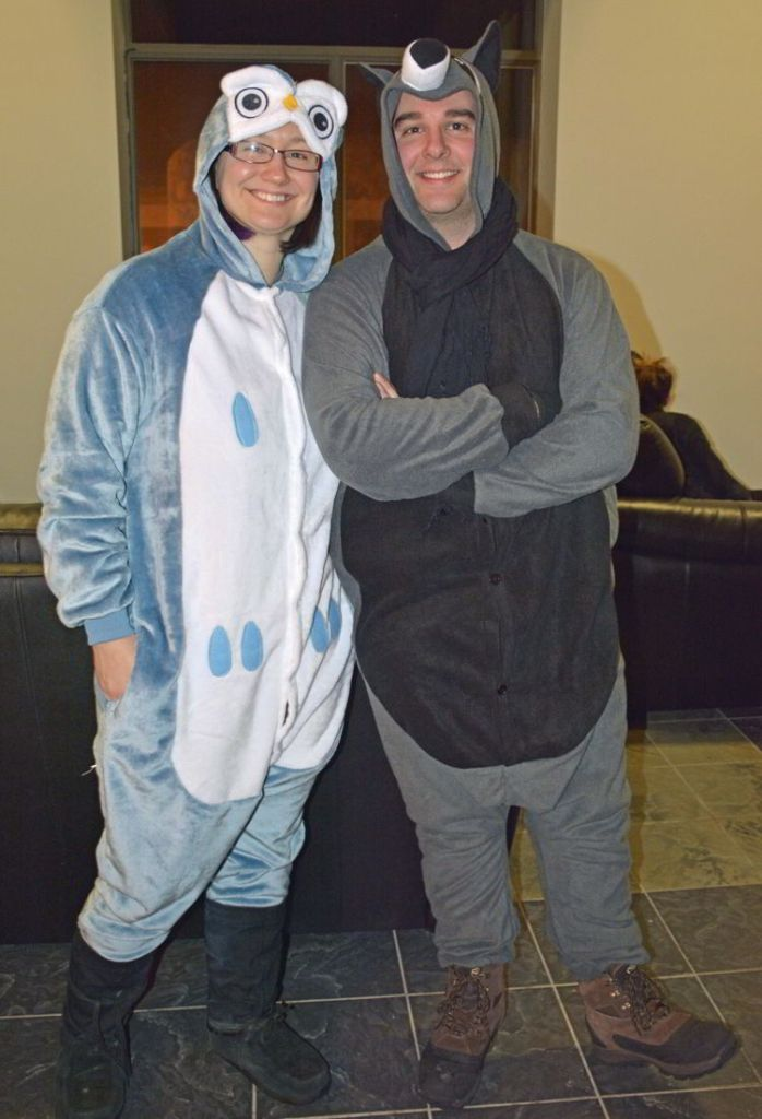 An image of two adults wearing fury animal pajamas with feet at the Hôtel de Glace in Quebec, Canada - Ice Hotel Quebec