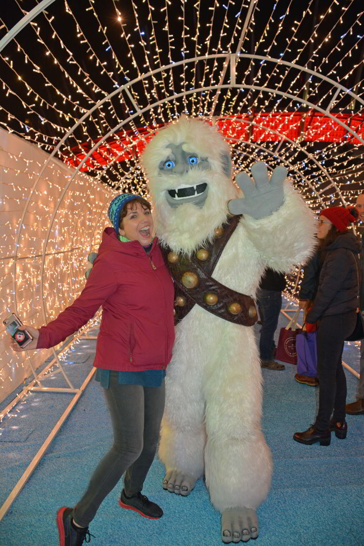 An image of a woman posing with the Abominable Snowman at the Aurora Winter Festival in Vancouver, BC Canada - Vancouver Christmas Lights