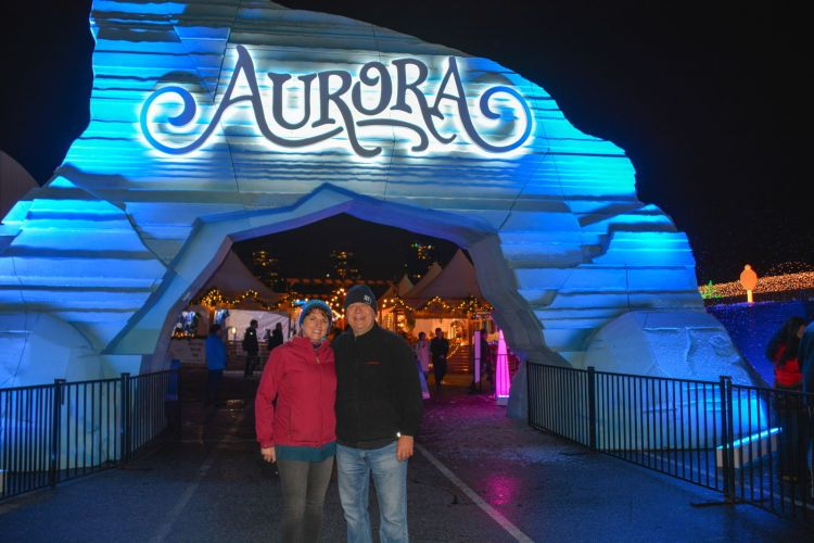 An image of a couple standing in front of the sign for the Aurora Winter Festival - Vancouver Christmas Lights