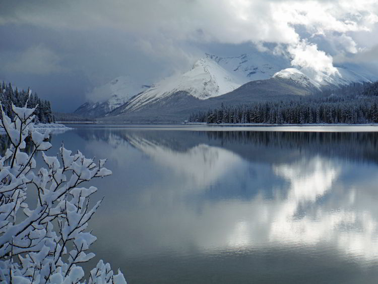 An image of Maligne Lake in early winter before the lake has frozen and with snow on the ground. Jasper National Park in Alberta, Canada  - Jasper in Winter - stunning photos