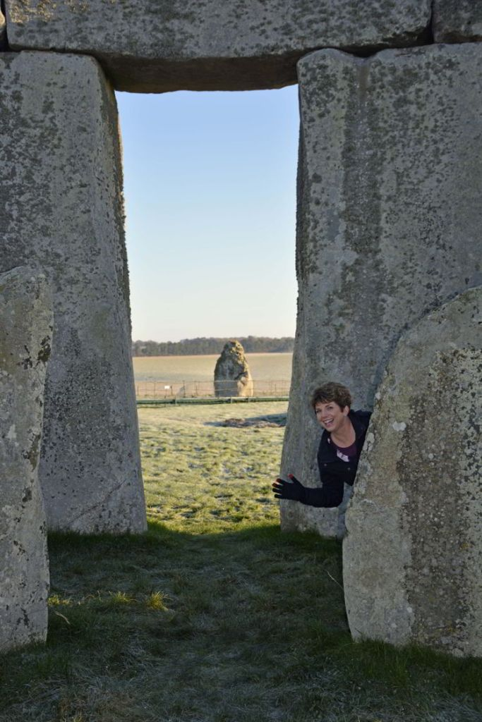 An image of a person beside the inner circle rocks at Stonehenge near Salisbury, UK - Stonehenge inner circle tours