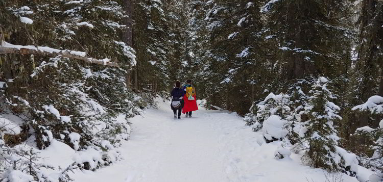 An image of a couple walking through a forest of snow covered trees on the ink pots hike in Banff National Park, Alberta - Johnston Canyon Winter Hike and ink pots hike