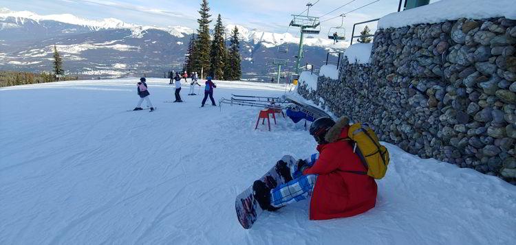 An image of a snow boarder adjusting his board at Marmot Basin in Jasper, Alberta - Jasper Skiing