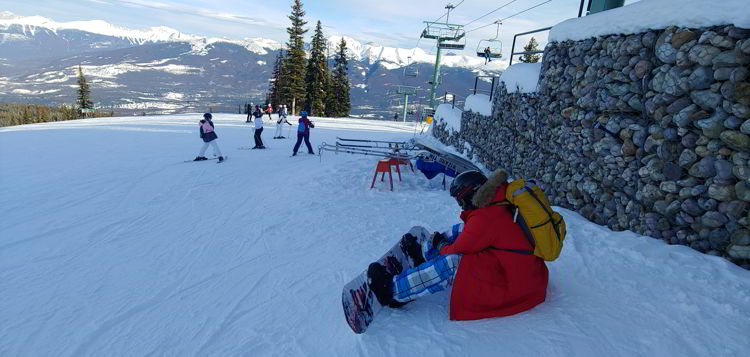 An image of a snow boarder adjusting his board at Marmot Basin in Jasper, Alberta - Jasper Skiing