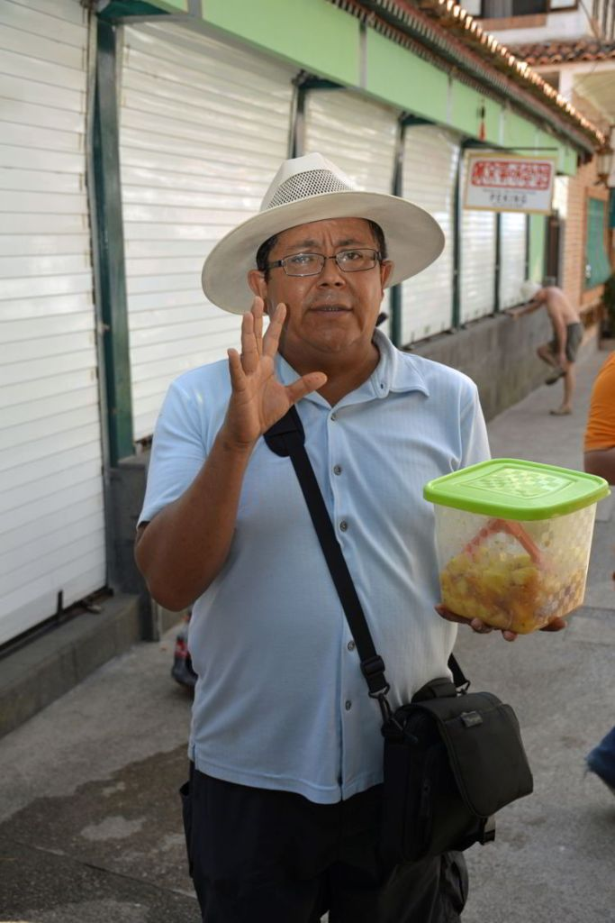 An image of a Vallarta Food Tours guide holding a container of salsa in Puerto Vallarta, Mexico - The best tacos in Puerto Vallarta