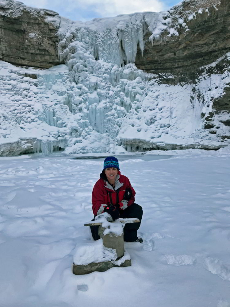 An image of a woman crouched in front of the frozen Crescent Falls - Abraham Lake, Alberta