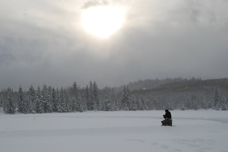 An image of a person sitting in a snowy field in Jasper National Park in Alberta - Alberta Hikes help you beat the winter blues