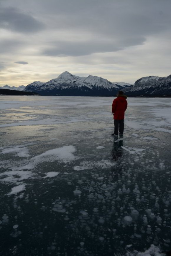 Image of a person standing on frozen Abraham Lake with methane bubbles trapped in the ice and a mountain in the background - Avoid the Winter Blues.