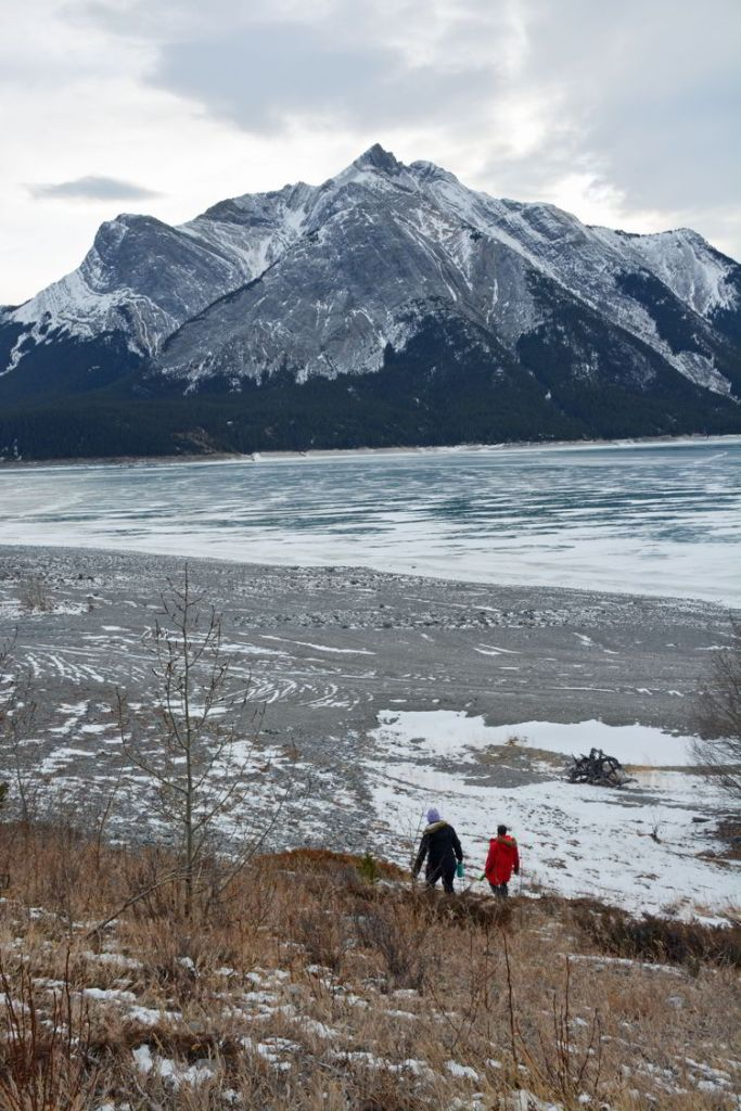 An image of two people walking down to the frozen Abraham Lake, Alberta.