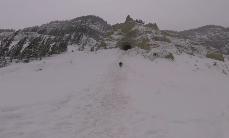 An image of a hiker climbing up a snowy hill to a cave on the Grotto Canyon hike near Canmore, Alberta