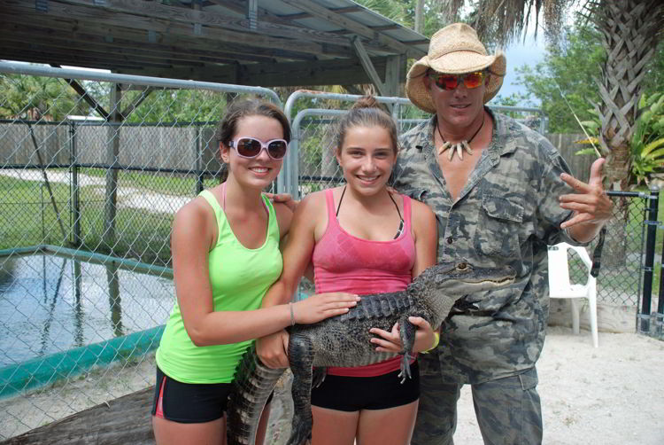 An image of two girls and a man holding a baby alligator at Wooter's animal sanctuary in the Florida Everglades.