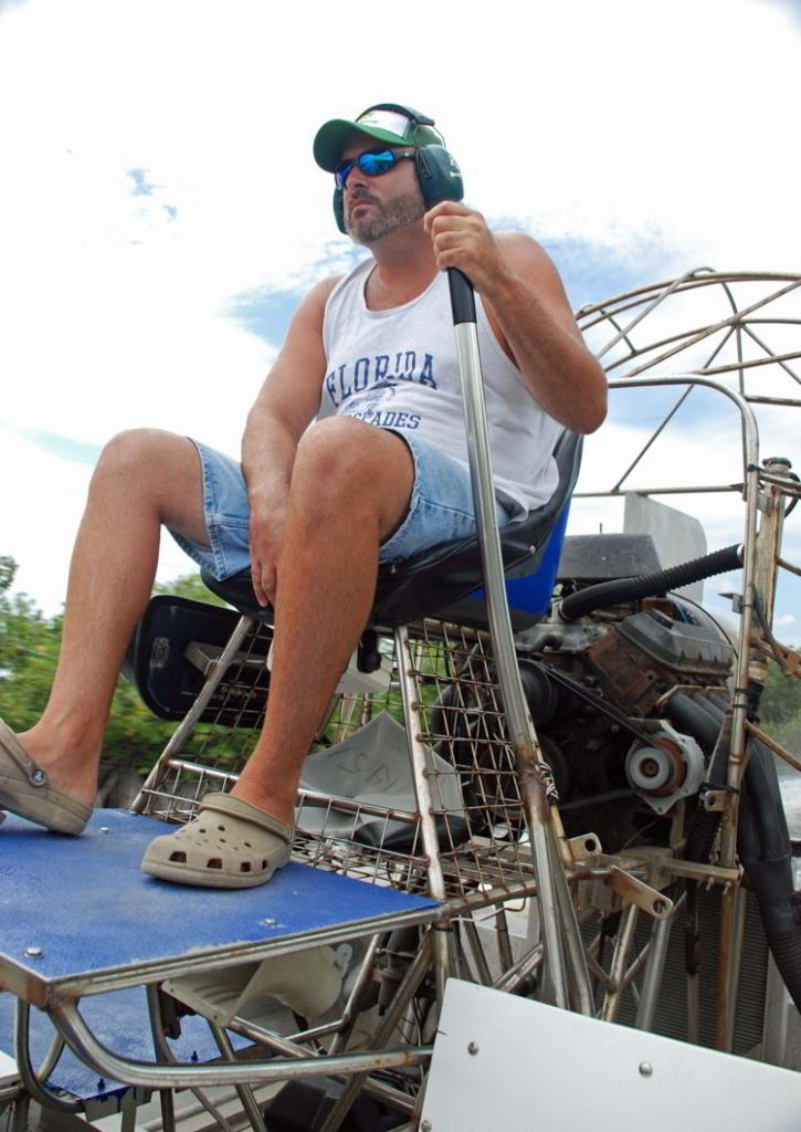 An image of a captain driving an airboat in the Florida Everglades