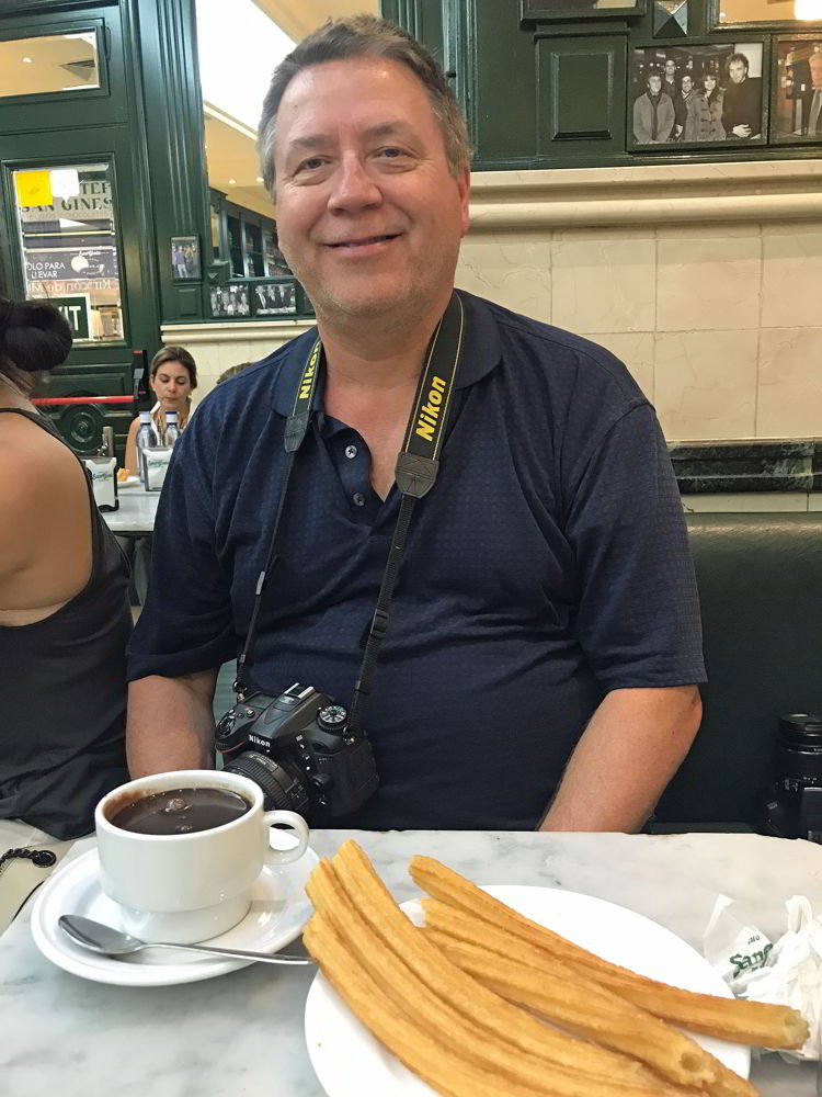 An image of a man sitting in front of a plate of churros and a cu pof hot chocolate in Madrid, Spain.