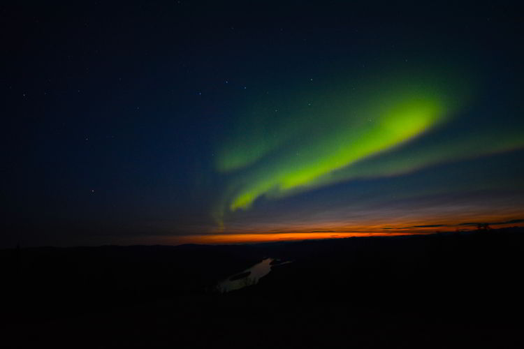 An image of a red and green aurora near Dawson City, Yukon in August.