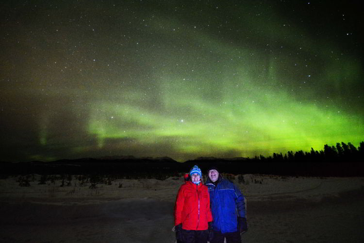 An image of two people standing in front of the Yukon northern lights outside Whitehorse in January.