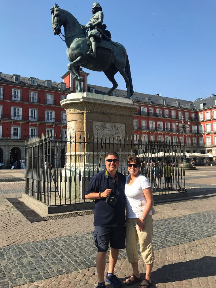 An image of two people standing in front of the statue of Phillip III in the centre of Plaza Mayor in Madrid, Spain.