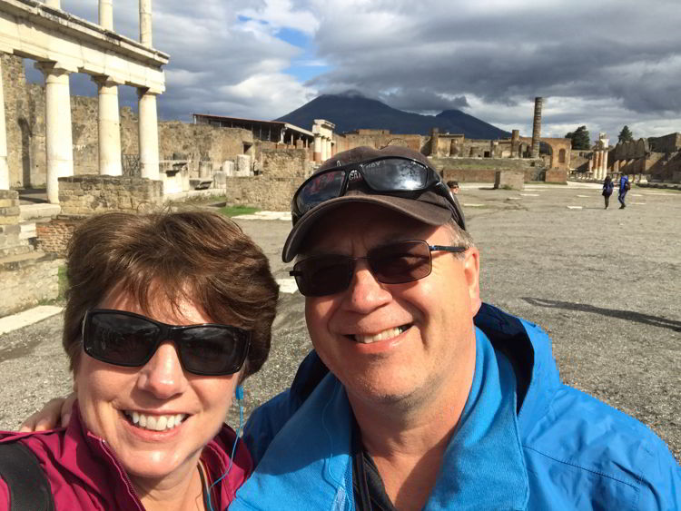 An image of two people standing in Pompeii with Mount Vesuvius in the background near Naples, Italy.