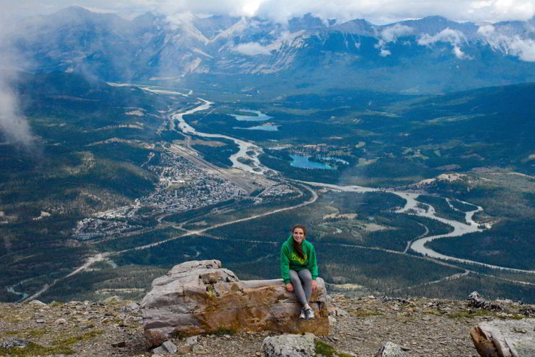 An image of a young woman sitting on a rock at the top of Whistler's Mountain in Jasper National Park, Alberta, Canada - Jasper hikes.