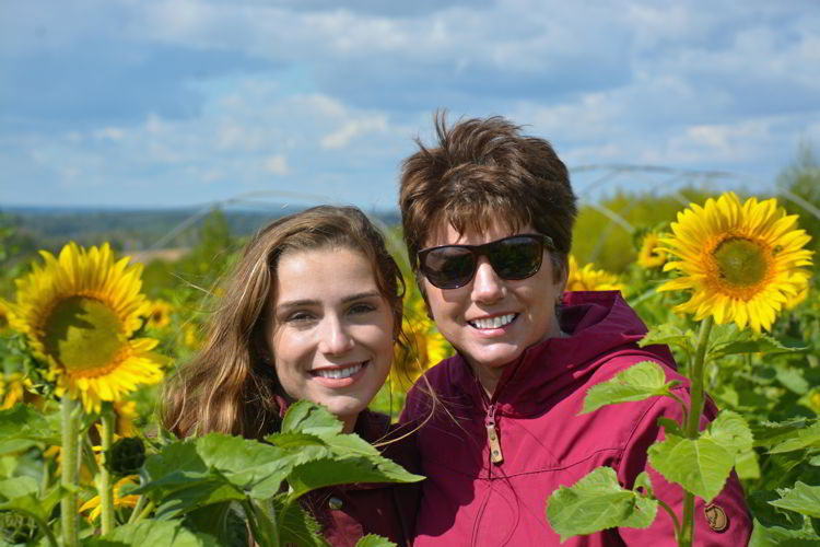 An image of a mother a daughter in a sunflower field at Bowden Sunmaze in Bowden, Alberta, Canada.