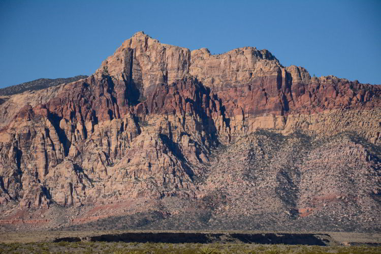 An image of a mountain with a red streak running through it at the Red Rock Conservation Area outside Las Vegas, Nevada.