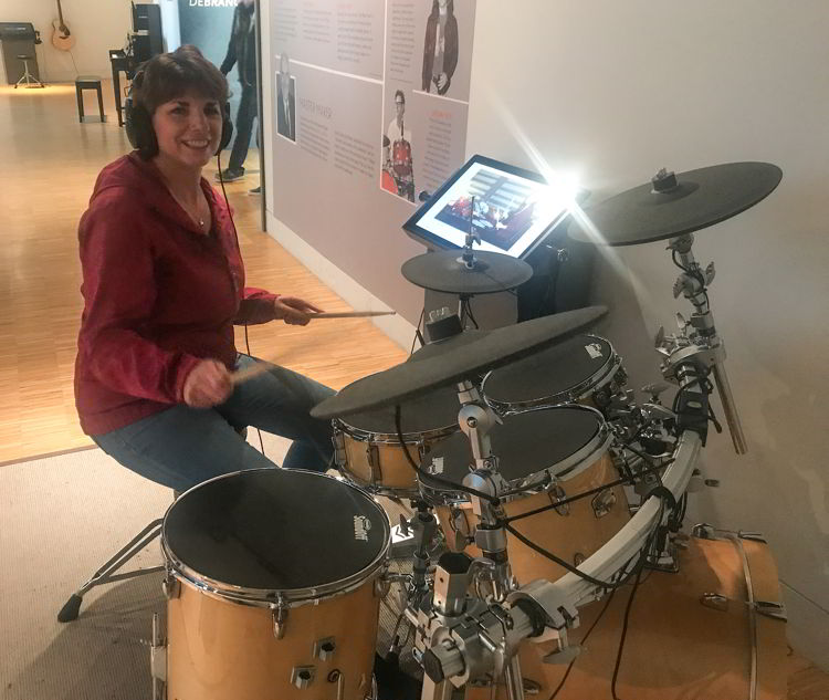 An image of a woman wearing headphones and playing a drum set.