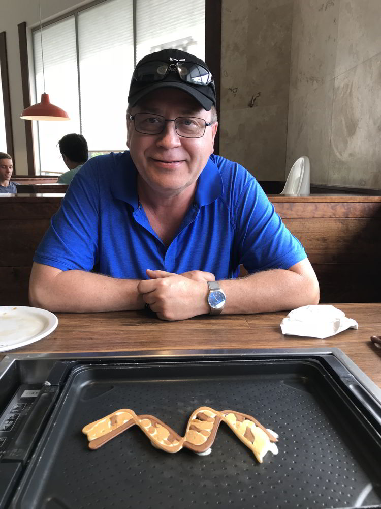 An image of a man with the pancake art he created at Slappy Cakes Restaurant in Kāʻanapali, Maui.