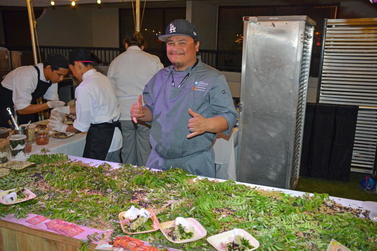 An image of a chef at a booth at the Hawaii Food and Wine Festival in 2018.