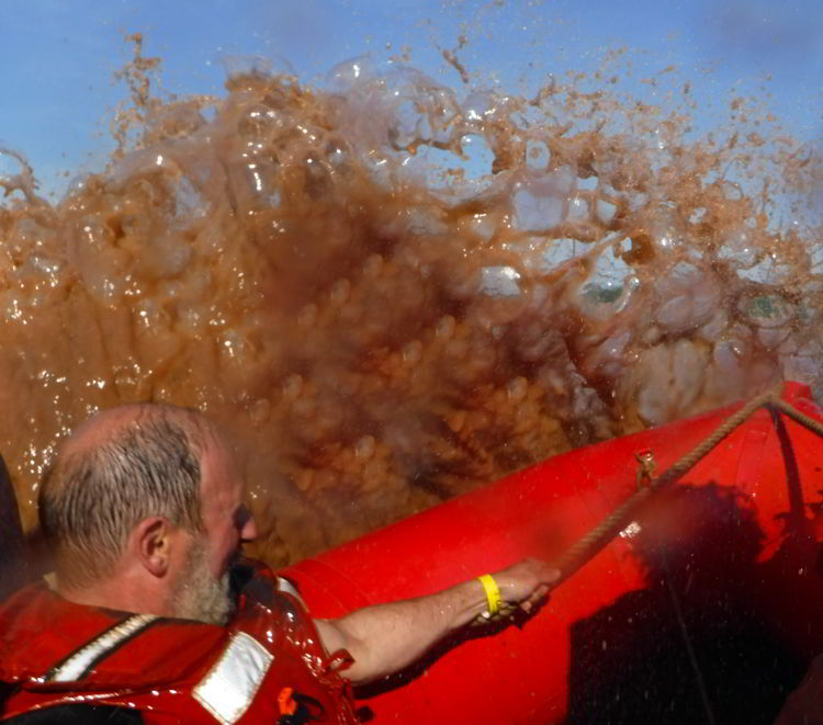 An image of a boat hitting the tidal bore on a tidal bore rafting excursion in Nova Scotia, Canada.
