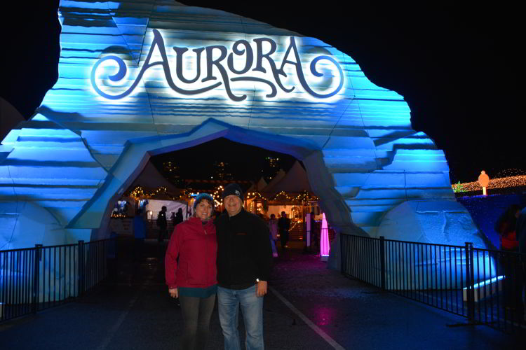 An image of two people standing in front of the entrance gate at the Aurora Winter Festival in Vancouver, BC, Canada.
