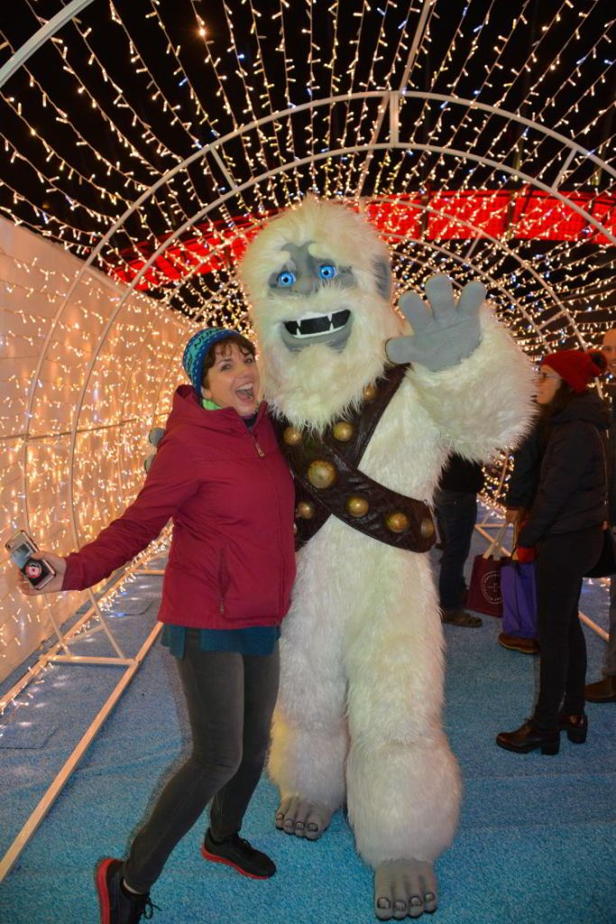 An image of a woman standing beside Yeti at the Aurora Winter Festival in Vancouver, BC, Canada.