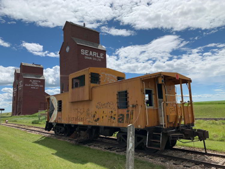 An image of the caboose and grain elevator in Rowley, Alberta.