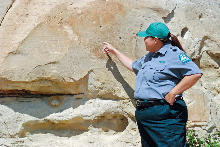 An image of an indigenous interpretor pointing at a petroglyph in Writing-on-Stone Provincial Park in Alberta, Canada.