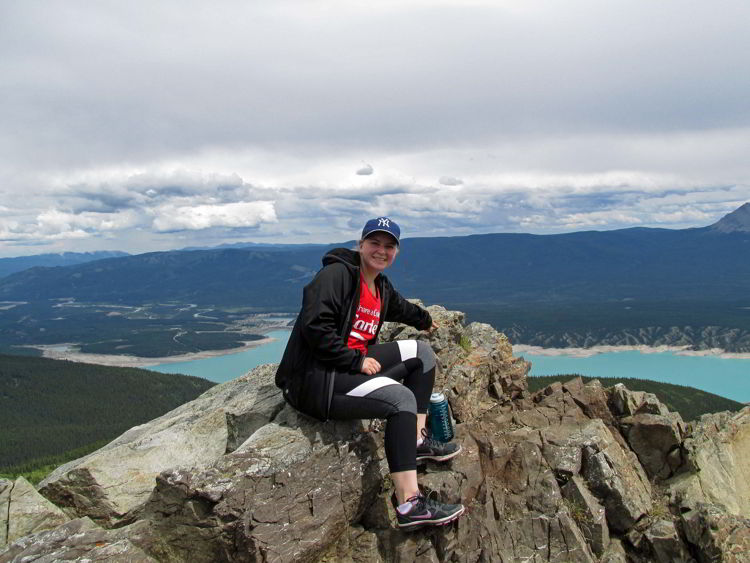 An image of a person sitting on a rocky viewpoint above Abraham Lake in Alberta, Canada.