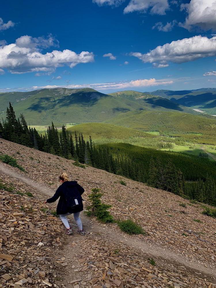 An image of a woman scrambling down the Nihahi Ridge trail in Kananaskis, Alberta, Canada.