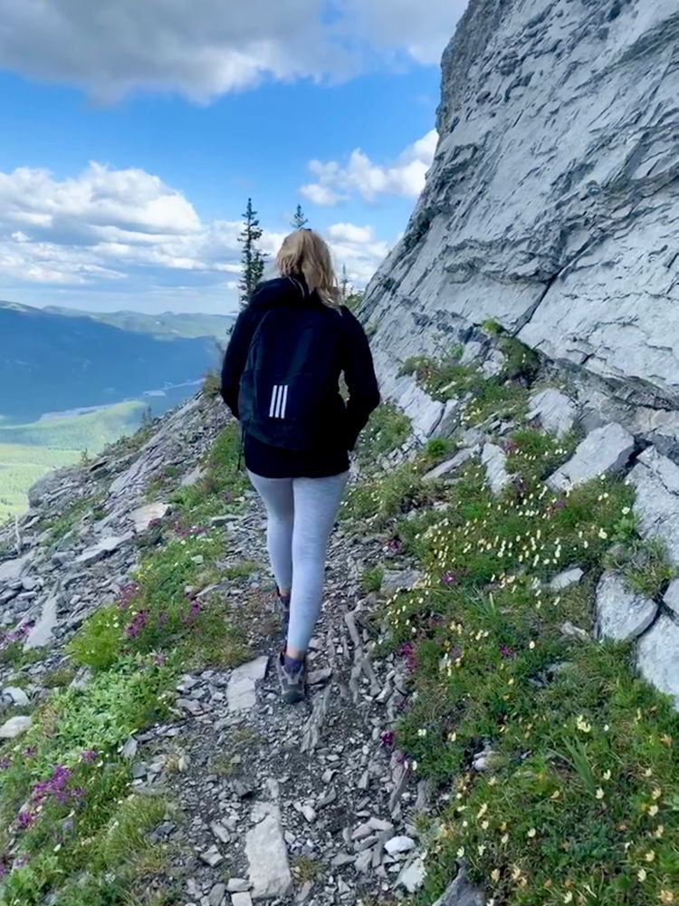An image of a woman hiking up the trail to Nihahi Ridge in Kananaskis, Provincial Park in Alberta, Canada.