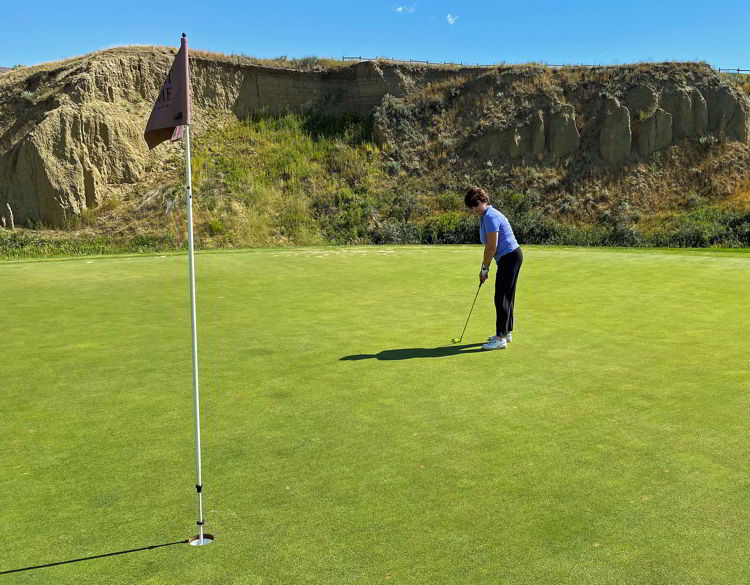 An image of a woman putting at Desert Blume Golf Course in Medicine Hat, Alberta, Canada.