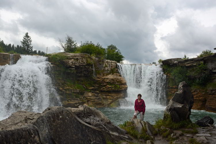 An image of a woman standing in front of Lundbreck Falls in Alberta, Canada. Crowsnest Pass road trip.