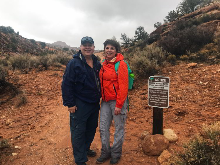 An image of a couple standing at the trailhead for Coyote Buttes North Wilderness Area in Utah, USA.