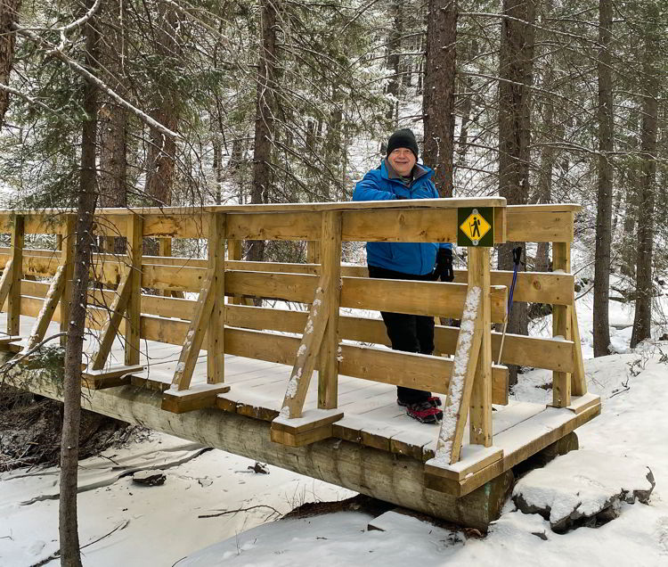 An image of a man standing on the wooden bridge on the Star Creek Falls hike in Crowsnest Pass, Alberta, Canada.