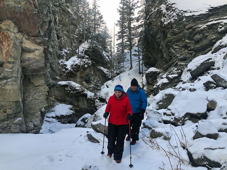 An image of a couple hiking in the canyon on the Star Creek Falls ice walk hike in Crowsnest Pass, Alberta, Canada.
