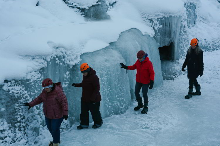 An image of a group of people walking along an ice formation in Maligne Canyon on a Jasper Icewalk.